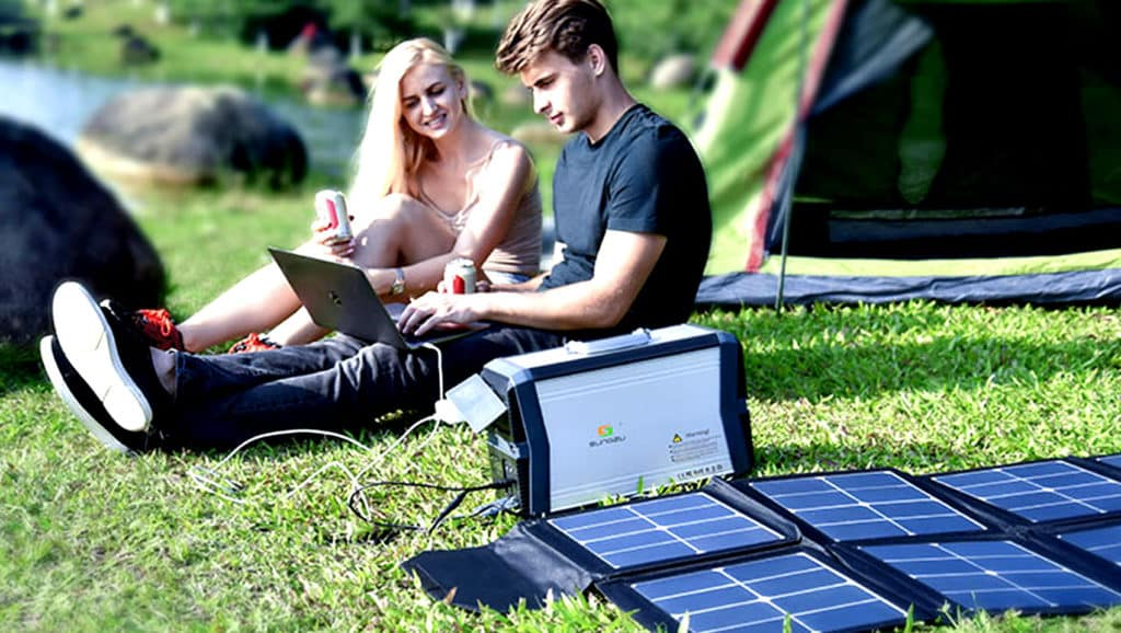 Couple-Sitting-On-The-Grass-Next-To-The-Solar-power-Bank